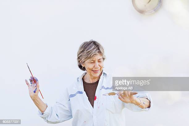 Happy senior female painter looking at brush against white wall