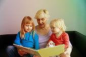 happy senior grandmother reading book for grandkids, grand parenting
