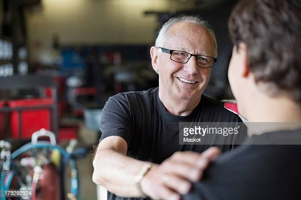 Happy senior male mechanic looking at coworker in auto repair shop