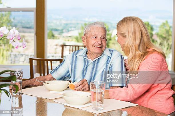 Happy senior man and adult daughter eating lunch at home