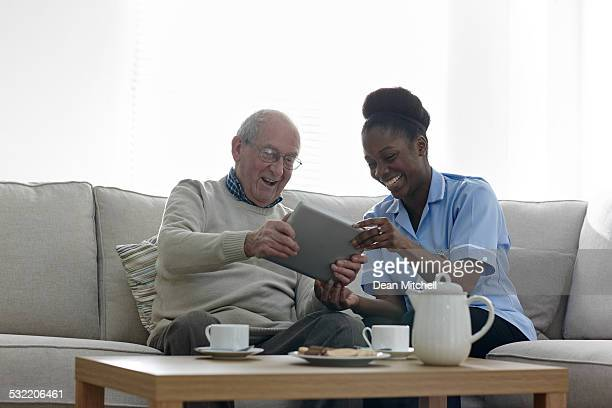Happy senior man and nurse using digital tablet at home