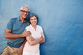 Portrait of happy senior man and woman together against blue background. Middle aged couple looking at camera and smiling with copy space on blue wall.