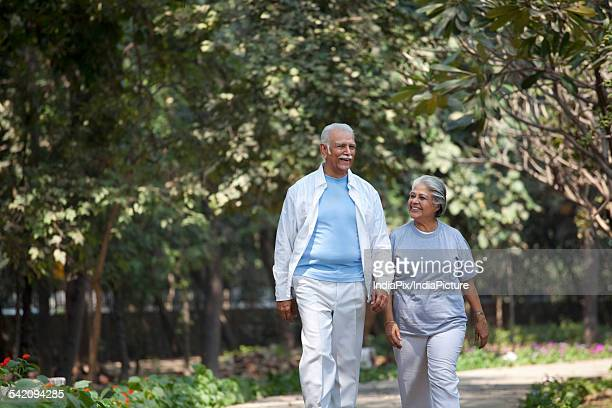 Happy senior man and woman walking at park