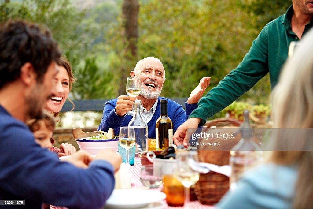 Happy senior man enjoying meal with family in yard : Stock Photo