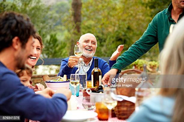 Happy senior man enjoying meal with family in yard