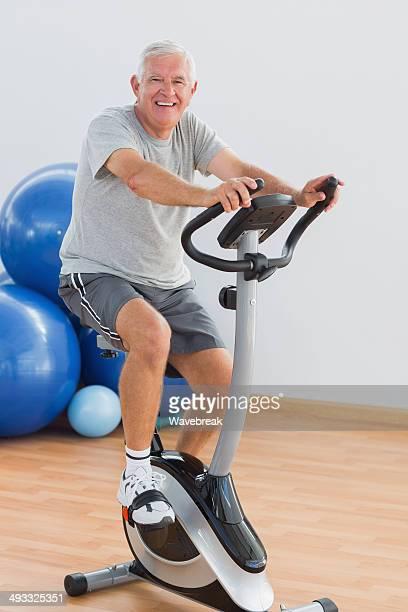 Happy senior man exercising at gym