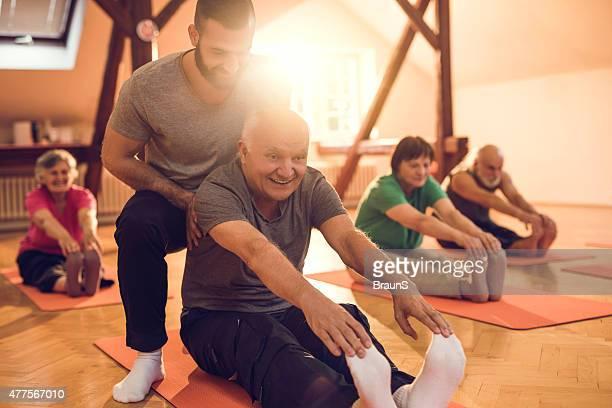 Happy senior Mann Training mit Hilfe eines persönlichen Trainers zurück.
