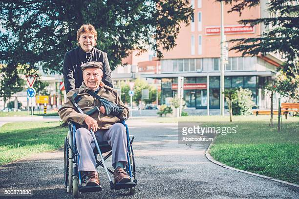 Happy Senior Man in Wheelchair and Grandson in the City