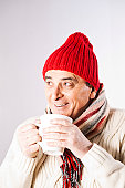 Happy senior man in winter clothes drinking cup of tea