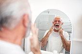 Happy senior man looking in the mirror.