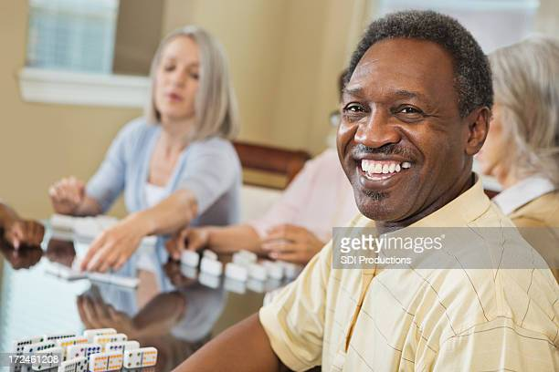Happy senior man playing dominoes with friends at home