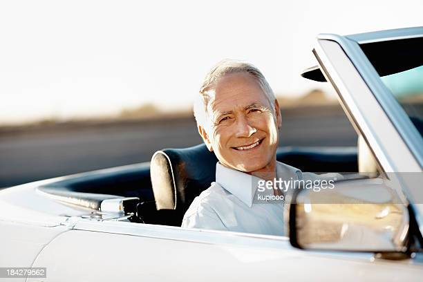 Happy senior man sitting in his car