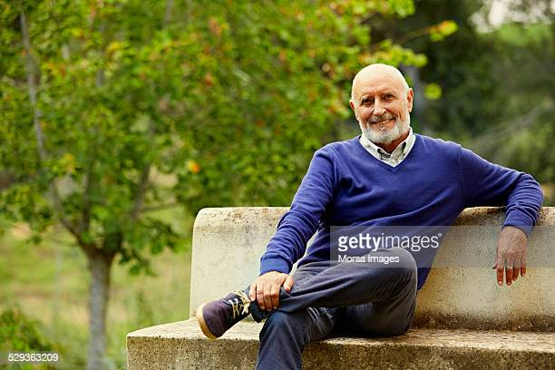 Happy senior man sitting on park bench