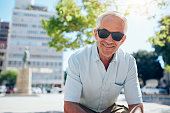 Portrait of happy senior man sitting outside in the city. Mature man with sunglasses outdoors on a summer day.