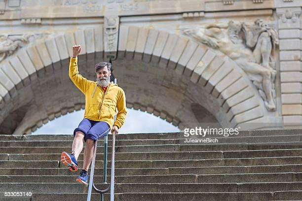 Happy senior man sliding down steps