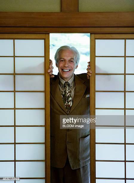 Happy Senior Man Standing Between Shoji