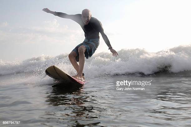 Happy senior man surfing