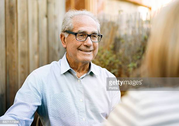 Happy senior man talking with woman in backyard