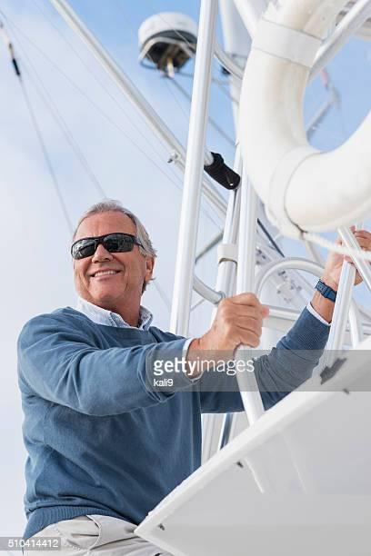 Glücklich leitender Mann mit Sonnenbrille Klettern auf Jacht