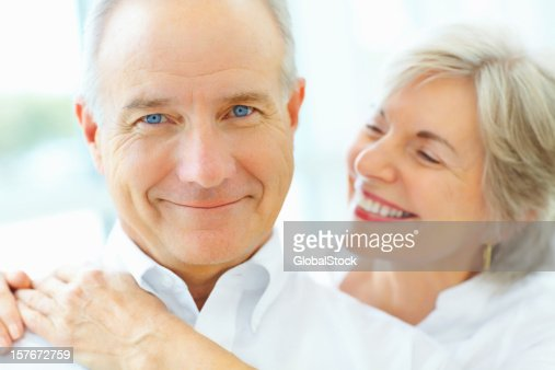 Happy senior man with smiling mature woman embracing from behind