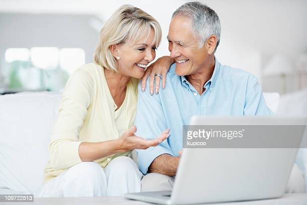 Happy senior man with surprised woman working on a laptop