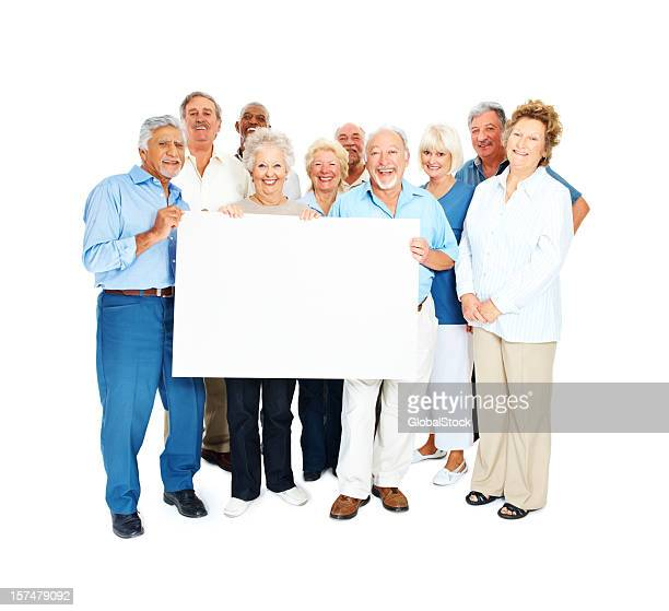 Happy senior men and women holding placard