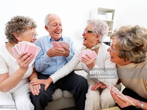 Happy senior men and women playing cards