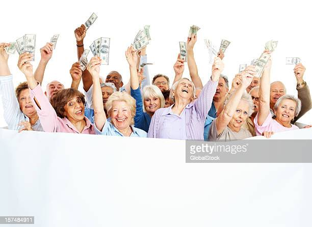 Happy senior people holding money with blank placard