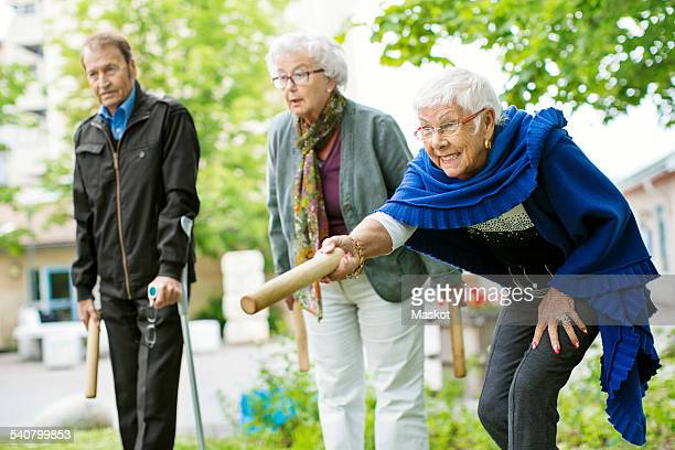 Happy senior people playing kubb game at park