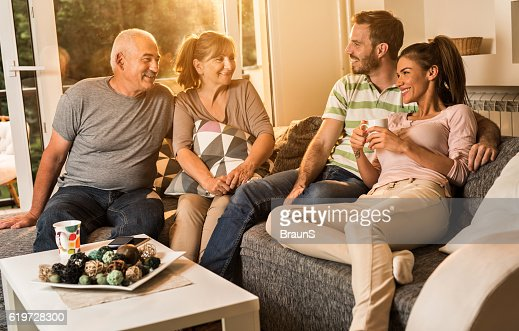 Happy senior people talking to young couple at home.