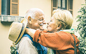 Happy senior retired couple having fun kissing outdoors at travel vacation - Love concept of joyful elderly and retirement lifestyle with man lovely watching wife in the eyes - Bright vintage filter