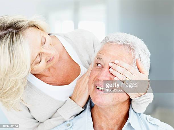 Happy senior wife covering eyes of her husband