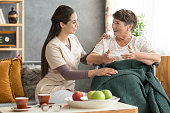 Happy disabled senior woman conversing with friendly caregiver