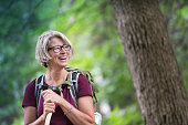 Enthusiastic senior woman backpacking in the forest