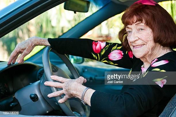 Glückliche senior Frau hinter der Rad des Wagens