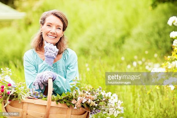 Happy Senior Woman Carrying Flower Basket While Gardening