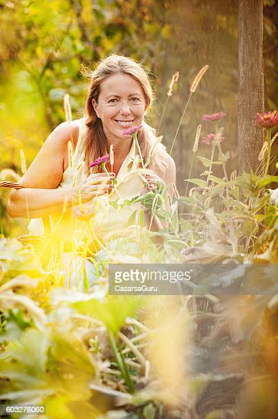 Happy Senior Woman Checking her Flowers