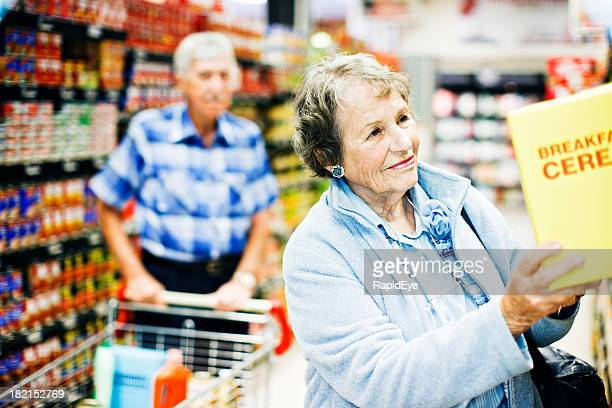 Happy senior woman finds favorite cereal in supermarket