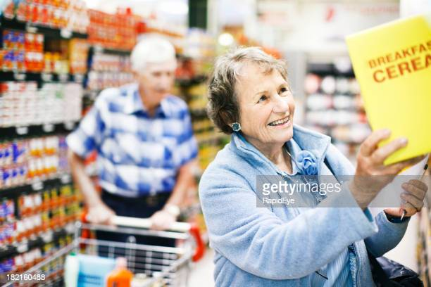 Happy senior woman finds favourite cereal in supermarket