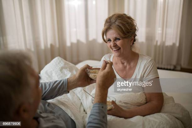 Happy senior woman having a breakfast in bed with her husband.