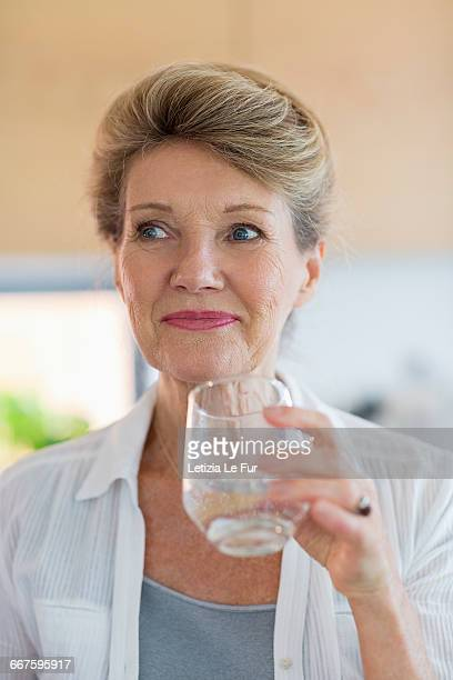Happy senior woman holding a glass of water