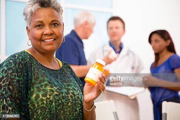Glücklich Ältere Frau für verschreibungspflichtige Medikamente.  Arzt, Patienten im Hintergrund.