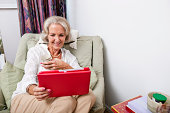 Happy senior woman looking at digital tablet on armchair in house