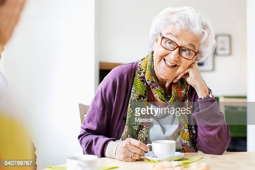 Happy senior woman looking at friend while having coffee at breakfast table in nursing home : Stock Photo