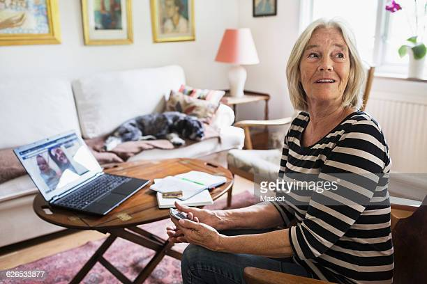 Happy senior woman looking away at home while dog relaxing on sofa