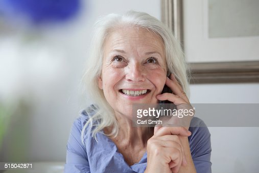 Happy senior woman looking up while answering mobile phone at home