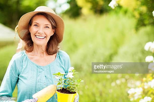 Felice Senior donna piantando Fiori nel giardino