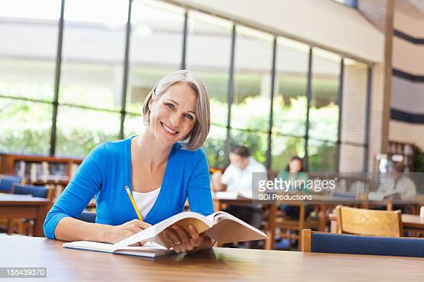 Happy senior woman reading Weiterbildung in der Bibliothek