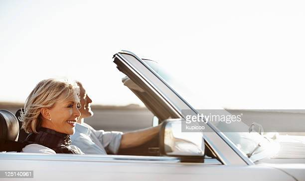Happy senior woman riding in a car with her husband