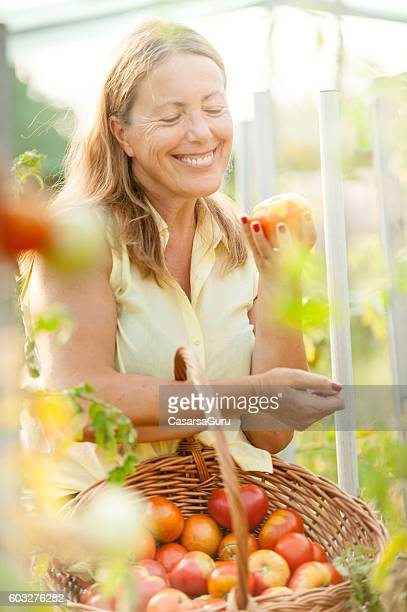 Happy Senior Woman Showing her Homegrown Tomato